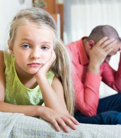 Portrait of small girl quarrelling with father at home